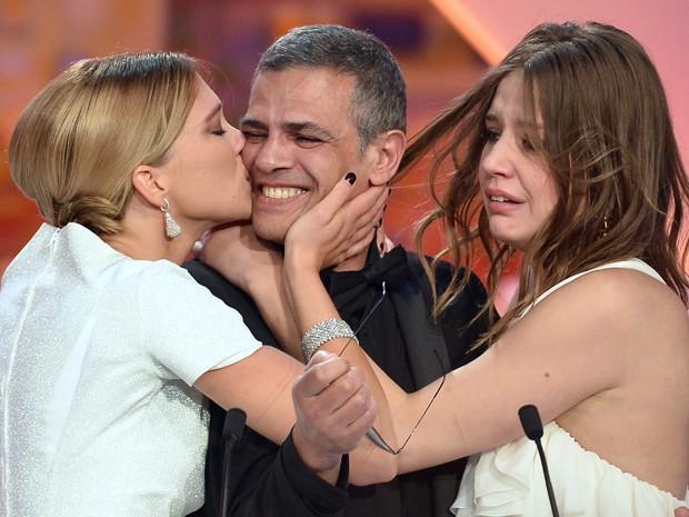 A atriz Lea Seydoux beija o diretor franco-tunisiano Abdellatif Kechiche, ao lado da atriz Adele Exarchopoulos, após o anúncio de que o filme protagonizado por elas e dirigido pelo cineasta ganhou a Palma de Ouro em Cannes (Foto: Alberto Pizzoli / AFP)