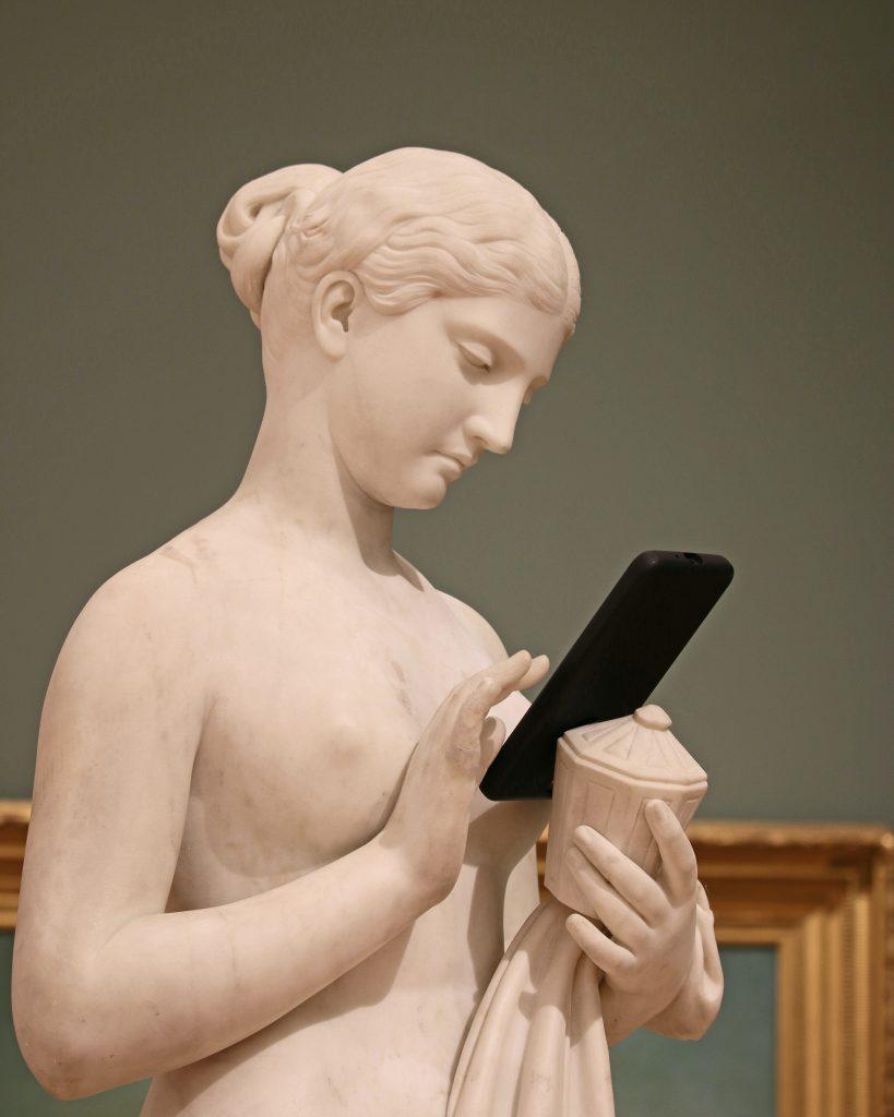 era da (des)informação - estátua renascentista segura um celular