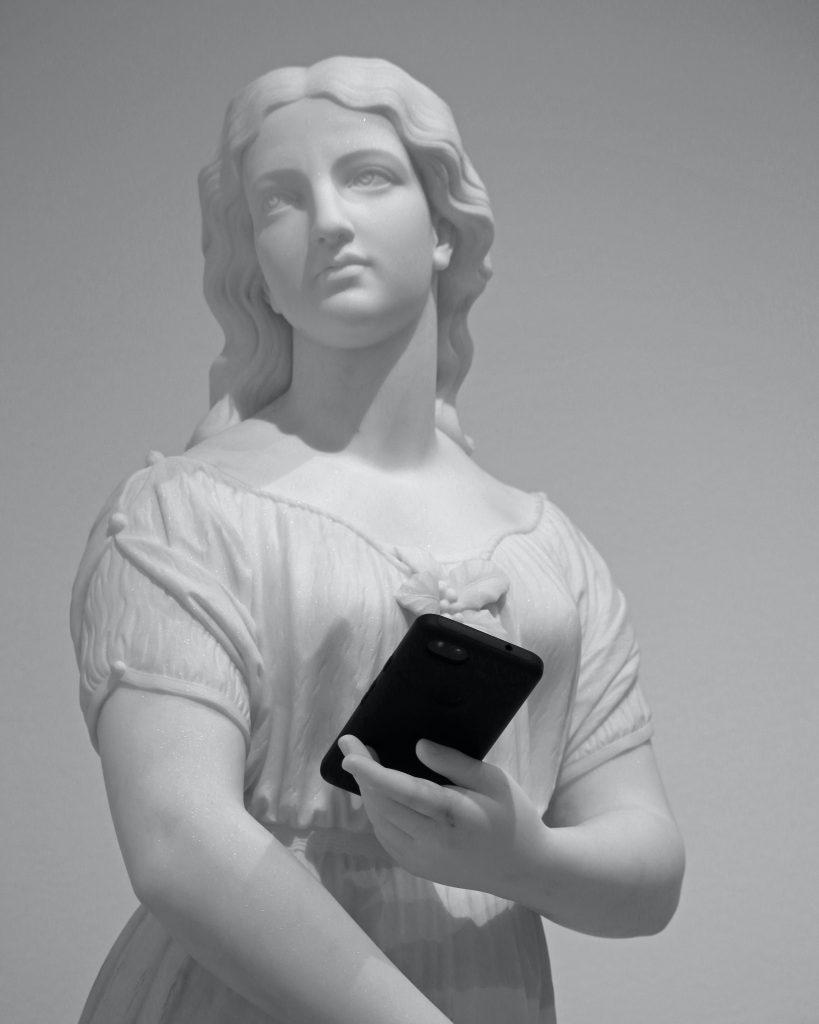 Era da (des)informação - Estátua renascentista segura um celular.