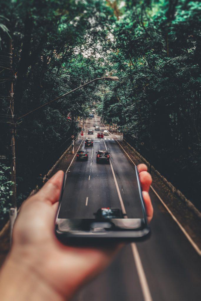 era da desinformação - montagem fotográfica faz avenida sair de dentro da tela de um celular.