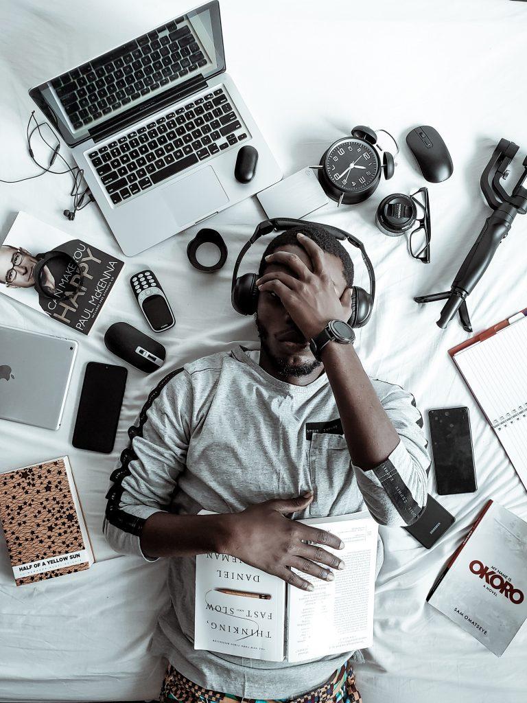 Era da (des)informação - homem negro é rodeado por itens tecnológicos. Sua posição demonstra esgotamento.